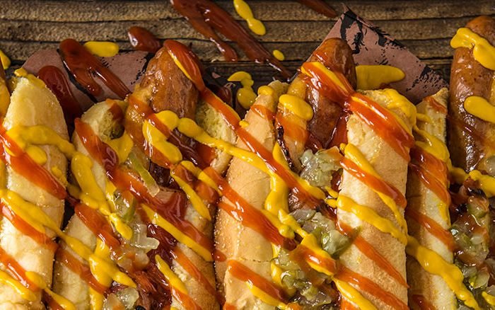 Everything is better with bacon. Take your dogs to to the next level with crispy bacon, melty cheddar cheese, and all your favourite toppings.